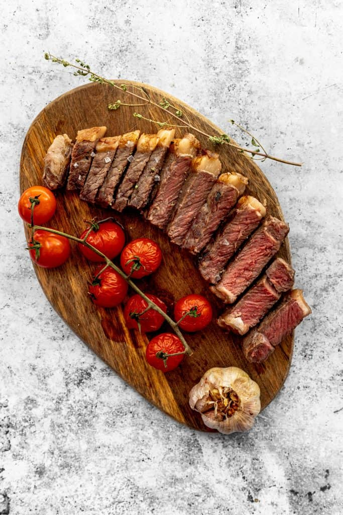 Sliced sous vide rib eye steak on wooden platter with cherry tomatoes and roasted garlic
