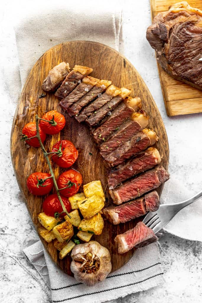 Sliced sous vide rib eye steak on wooden platter