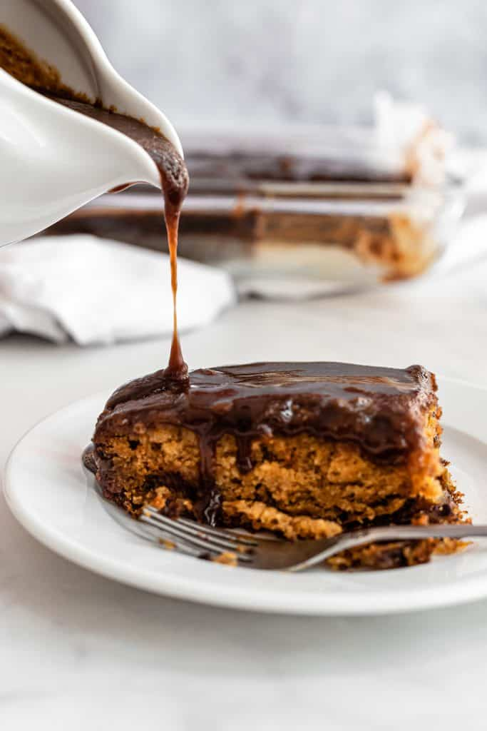 toffee sauce being poured on sticky date cake