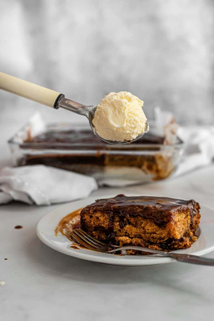 scoop of vanilla ice cream held over date cake