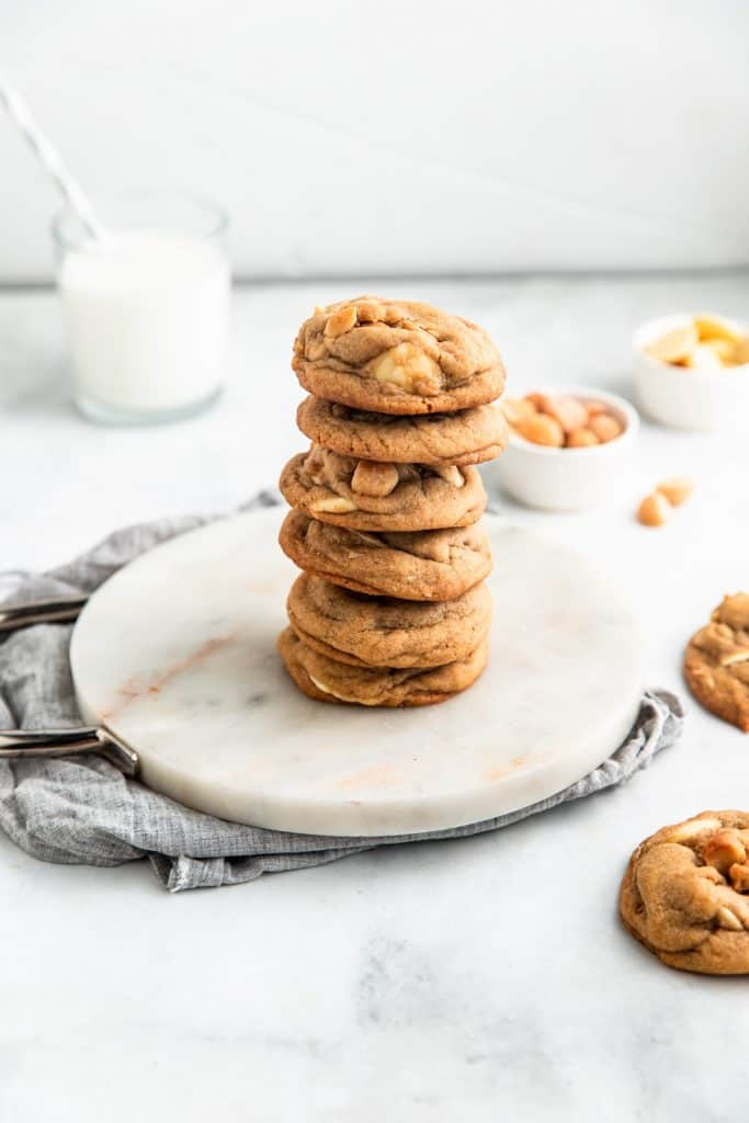 stack of white chocolate macadamia cookies with a glass of milk in the background