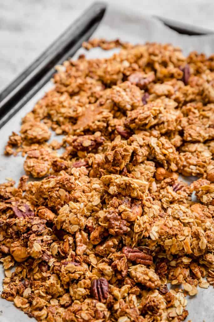 close up of tahini granola on parchment paper in baking sheet