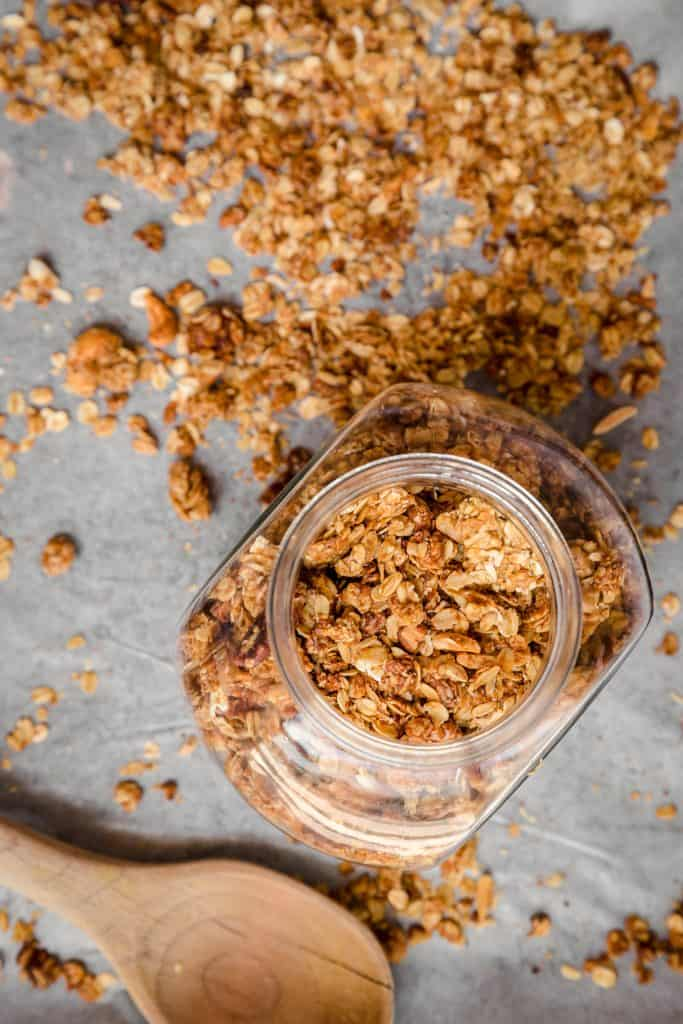 granola in a big glass jar with more scattered around