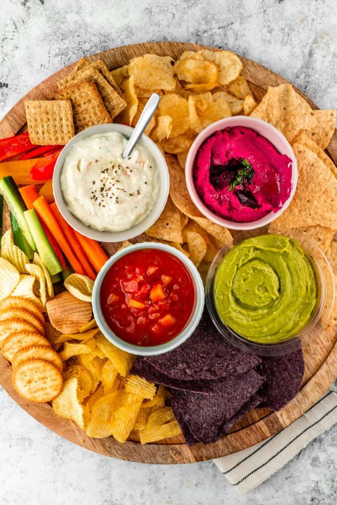 Chips and cracker platter with different dips in small bowls