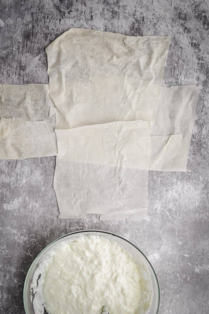 two phyllo sheets crossed on top of each other with a bowl of ashta